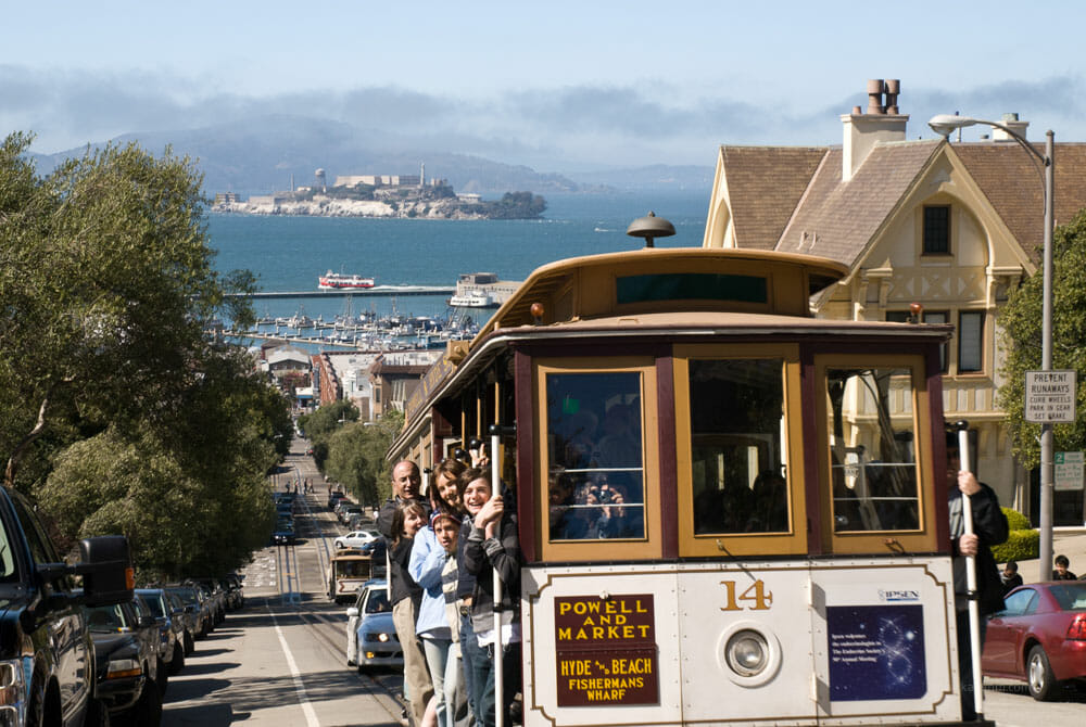 A cable car heading up Nob Hill, with Alcatraz in the background