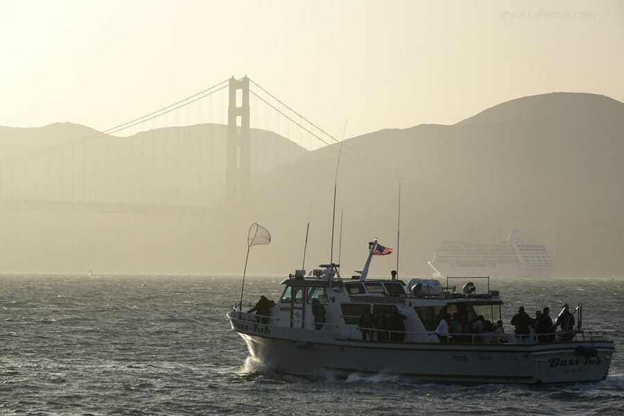 Fishing boat and cruise ship at the Golden Gate Bridge